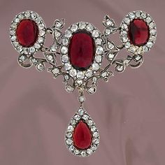 Early 19th Century Garnet and Diamond Brooch.Beautiful silver over 14K yellow gold pin highlighting three oval cabochon garnets (7.45 carats) accented with rose cut diamonds (82 total, 1.50 carats total weight) in a delicate foliate motif throughout with a drop pear shaped garnet (1.50 carat) surrounded by rose cut diamonds.