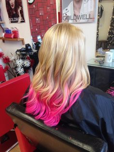 Blonde hair with a pink ombré on the length finished with curls