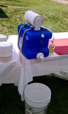 Improvised hand washing station. I like the paper towels on top!  Great idea for camping kitchen set up.