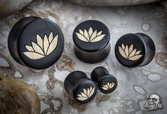 Gaboon ebony plugs with ash wood lotus flower inlays  in stock at Pinky's Piercing & Fine Body Jewelry