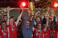 Manager of Bayern Munich Pep Guardiola lifts the trophy with his team to celebrate victory after the DFB Cup Final match between Bayern Muenchen and Borussia Dortmund at Olympiastadion on May 21, 2016