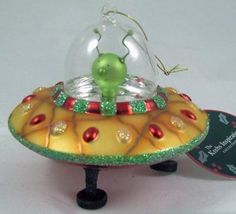 Flying Saucer with Alien Pilot Christmas Ornament!  This classy glass construction Christmas ornament complete with clear glass dome protecting the little green alien with little green antennae is going to go great on your Christmas tree!  Set yourself apart and express your own sci-fi, UFO interests this Holiday season or give it as a gift to that special someone who just can't get enough X-Files!