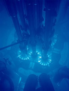 When high-energy charged particles pass through matter, they emit light, known as Cerenkov radiation.  In the water of a cooling tank it is a beautiful blue.