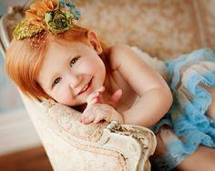 precious little redhead posing in chair