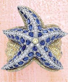 A Sapphire and Diamond 'Starfish' Cuff Bracelet  Of starfish design, the sculpted cuff bracelet entirely decorated with oval-cut sapphires and circular-cut diamonds and coloured diamonds, mounted 18K white gold.
