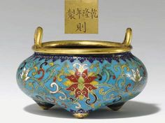 Cloisonne Enamel Tripod Censer, Qianlong period, Qing Dynasty.  The compressed body decorated with a frieze of continuous lotus scroll below a blue ruyi band repeated around the tops of the conical supports which are separated by three floral sprays on the underside surrounding the inlaid gilt-bronze plaque inscribed with the mark, with a pair of loop handles rising from the rim.