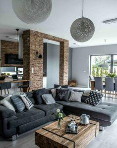 formidable studio avec un salon gris et blanc, canapé gris anthracite, superbes suspensions, mur en briques, table en bois brut, salon style industriel