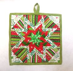 A folded star potholder in Christmas theme fabrics use as wall decor or as a hot pad or trivet to protect your counter tops and table from hot