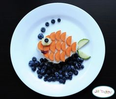 Blueberries make the ocean in this cute lunch snack for children. A sandwich is cut into the shape of a fish body and the scales are made from carrots, making a gold fish. Cucumber is added for the tail.
