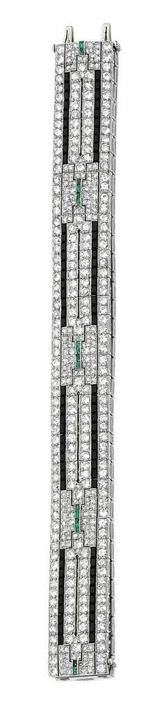 ONYX, EMERALD AND DIAMOND BRACELET, CIRCA 1930.  The articulated band pierced in a geometric pattern, millegrain set with circular-, single- and brilliant-cut diamonds, to the calibré-cut onyx and emerald accents, length approximately 190mm, one small emerald deficient.