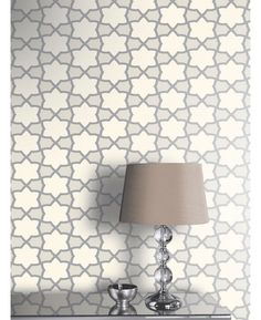 This beautiful Rio Geometric wallpaper features a stylish interlocking star lattice design, with textured silver glitter detailing and a subtle metallic sheen for added effect.