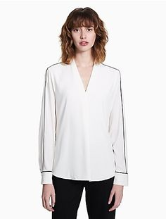 a lightweight, refined top made with a v-neckline, piped trim, long sleeves with button cuffs and a curved high low hem.