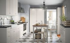 A medium size off-white kitchen with black worktops and chrome-plated handles and knobs. Combined with a stainless steel extractor hood and a beige cooker.