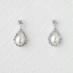 Cubic zirconia drop earrings of a CZ teardrop cradling a white glass pearl. Post back, 1 inch long. Rhodium plated, grade AAA cubic zirconia, glass pearls and lead free.