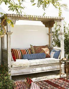 Coin sieste dans le jardin via une banquette à baldaquin