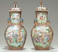 A PAIR OF 'MANDARIN PALETTE' VASES AND COVERS  Circa 1785  Each of baluster form with a pair of handles in the form of blue spotted, gilt and iron-red masks grasping gilt rings, painted front and back with large Chinese domestic scenes set in lakeside gardens, the panels edged in gilt bamboo and reserved on a 'Y'-patterned ground, colorful Buddhist lion knops.