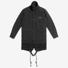 Black parka with inner wool layer and outer Japanese nylon layer, featuring a fishtail silhouette with adjustable cotton drawstring. Interior nylon adjustment strap with tonal matte D-rings. Front fla