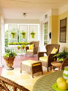 Like the trellis idea for privacy; love the sunny look of bright cushions and greenery with darker patio furniture.
