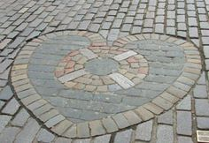 """At site: """"...a memorial to the many hearts which must have been pounding away on this very spot before being executed."""" Wikipedia: """"The Heart of Midlothian is a heart-shaped mosaic built into the roadway...in the High Street section of the Royal Mile in Edinburgh. ...it records the position of the...Old Tolbooth [15th c. to 1817]...the administrative centre of the town, prison & [a site] of public execution. The building features in Sir Walter Scott's [1818] novel, 'The Heart of Midlothian'..."""""""