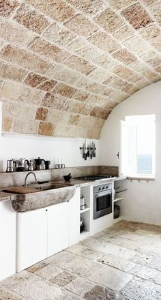 Rustic kitchen with vaulted stone ceiling and concrete sink. #italy #architecture #decor