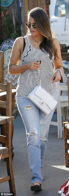 Low-key look: Khloe Kardashian Odom paired the jeans with a striped vest top and flat sandals while Kourtney Kardashian looked sultry with her curled hair and heavy make-up