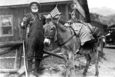 One of the great army of prospectors who still pans for colors Estes Park/near Grand Lake. A prospector poses near a donkey in either Estes Park or Grand Lake, Colorado. The donkey has saddle bags and U. S. flags attached to its tack. A car is in the background. Date1922. Source: A. W. Spring. Courtesy: Western History/Genealogy Department, Denver Public Library, Denver, Colorado (USA).