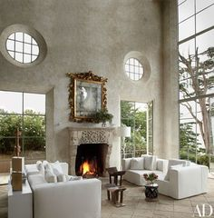 The living room walls are sheathed in frescoed plaster; a 17th-century Italian gilt-wood mirror is displayed above an antique Cypriot fireplace. Shapiro designed the chairs, the wood stools are 19th-century Ghanaian, and the white-painted cast-bronze floor lamp, by Patricia Roach, is from Studiolo | archdigest.com