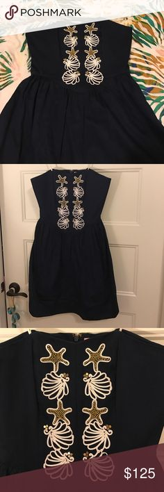 NWOT Lilly Pulitzer navy seashell dress This is a beautiful dress, never worn! I don't want to part with it but it just doesn't fit. Its a dark navy with white piping and gold beading that make up the seashell and starfish pattern. It's strapless and structured at the top with a full skirt Lilly Pulitzer Dresses Strapless