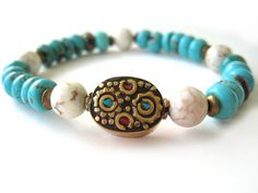 Beaded stretch bracelet featuring 8mm turquoise magnesite rondelle beads, 8mm white magnesite beads and a Tibetan focal bead with brass (inlaid with turquoise and coral chips). A great versatile handmade bracelet, this statement piece can be worn alone or stacked with other Rock & Hardware bracelets for a stylish option. A wonderful addition to your wardrobe!