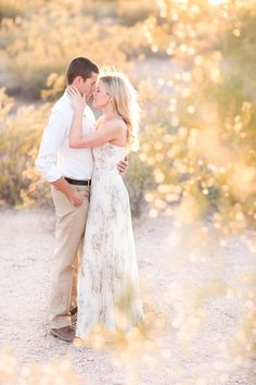 Gorgeous Papago Park engagement session. So many details made this session so special. A Navajo blanket for cuddling, a Fedora hat for her,  flowered chiffon full length dress, and of course the perfect golden desert light!