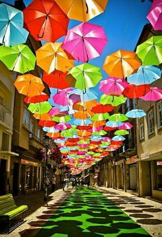 A creative cute way of providing shade as the bride walks down the aisle with all the colorful umbrellas hanging high up above (: