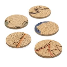 Topo Coasters represent the real topography of our favorite places. The  elevation changes are illustrated with layers of cork. Cork is an amazing  natural material. It is absorbent yet dries quickly. It grows as bark on  the Quercus Suber, or Cork Oak, tree. Best of all, harvesting the cork does  not harm the tree. The back of each coaster is a layer of veneer engraved  with the geographic coordinates of the location depicted by the topography  on the front. We hope the Topo Coasters…