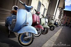 #Vespa - Line-up of Italian scooters parked on the pavement.