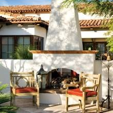 A two-way fireplace warms those on both sides of the courtyard wall via Phoenix Home & Garden