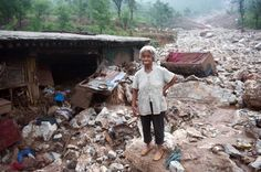 """An elderly woman stands by her damaged home in the devasted area in Beijing on July 26, 2012, after the worst rainstorms in six decades pounded the capital city on July 21 leaving the metropolis flooded and tens of thousands of people stranded in surging waters.  Authorities in Beijing said they would begin to """"strike"""" out at online critics of the government response to recent record flooding, while declining again to release updated casualty tolls. (Photo by AFP)"""
