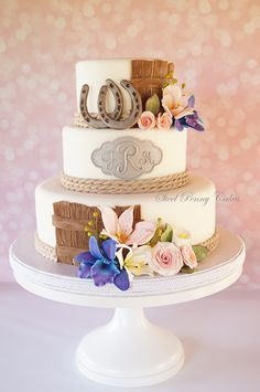 - Here's my take on a western themed wedding cake. I didn't want to go in the direction of an all brown cake or use any cow spots. I made a monogram plaque in silver to give the feel of a belt buckle, edible rope borders, wooden fence panels for a bit of brown, edible horseshoes, and sugar flowers- blue bomb orchids, pink roses, alstroemerias, and calla lilies.