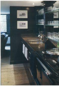 Zwarte keuken met spiegels en glazen planken. Het luxe gevoel van een restaurant voor in huis.