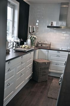 Love the white cabinets with silver. The shiny white tiles & the wood countertop