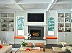 Chic living room with beadboard lined white built-ins, window seats with orange cushions flanking fireplace, beadboard coffered ceiling, gray & orange skirted ottomans, champagne leather tufted modern chairs and ivory sofa.