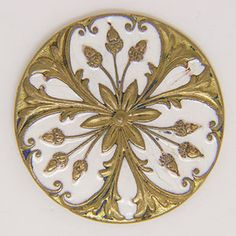 """White champlevé enamel covers part of the top of this antique brass button. Brass acorn and floral patterns contrast with the light enamel. The button measures 1 3/8"""" in diameter."""
