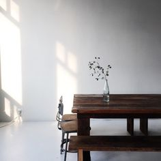 A rustic wood farm table in a white room with natural light filtering in. Sunday Suppers. A minimal, organic, rustic, modern, serene, slow living style vibe.