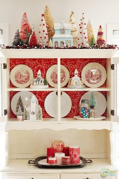 Super cute china cabinet decorated for Christmas. Lots of bottle brush trees, glitter houses  and lots of aqua and red!