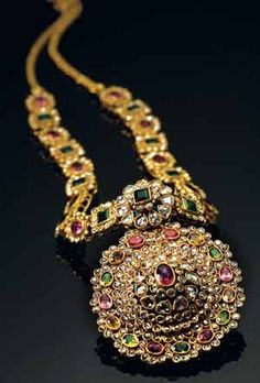 From Tanishq, India  An unusual blend of multicolour tourmalines with uncut diamonds come together in this strikingly elegant center piece.