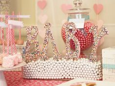 Cover wooden letters in candy sprinkles for a cute and easy centerpiece!  Hearts & Sprinkles Baby Shower Theme Ideas! Colorful sprinkles make this baby shower come alive with cuteness! So many adorable ideas that are affordable and easy for anyone to do!
