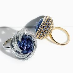 Exquisitely faceted tanzanites are surrounded by whirlpools of diamonds and sapphires in these intricate platinum and gold settings.