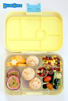 Brazilian cuisine inspired Yumbox lunch: cheese rolls, grilled pork with beans and corn, olives, tomatoes, cucumbers, cheese, passion fruit and   some nuts and raisins for a snack.