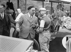 Tazio Nuvolari at the Ulster TT race, 1933. Tazio Nuvolari engaged in conversation with Hugh McConnell, the race organiser. Nuvolari won the race, driving an MG Magnette.The Italian was one of the legendary figures of the 'golden age' of motor racing in the 1930s. The 'Flying Mantuan' as he was known, moved to car racing in 1924 after a successful career racing motorcycles. His skill and daring took him to 200 major race victories and he was European Grand Prix Champion in 1932.