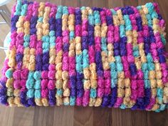 Hand knitted marshmallow/pom pom blanket in beautiful spring colours.
