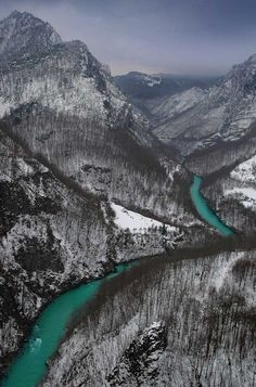Tara Canyon in Winter with its green water which contains mainly calcium from limestones. Crystal clear waters of Tara, which have light blue and green colour, made its canyon in rough limestone mountains even before the Ice Age. Water has carbon dioxide in it which turns calcium carbonate into calcium bicarbonate that dissolves in water. - Montenegro