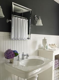 source: Bella Mancini Design Beautiful beachy cottage bathroom design with black walls paint color, beadboard, rectangular pivot mirror, glossy white porcelain pedestal sink washstand, polished nickel faucet & sconces and white bathroom cabinet Dining Room Wainscoting, Wainscoting Bathroom, Beadboard Backsplash, Herringbone Backsplash, Wainscoting Height, Black Wainscoting, Wainscoting Panels, Wainscoting Ideas, Travertine Backsplash